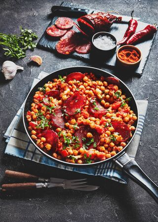 close-up of Garbanzos fritos, hot Chickpea stew with sliced chorizo, ham, tomatoes and spices in a skillet on a concrete table with ingredients, spanish cuisine. Stok Fotoğraf