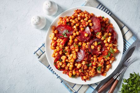 Garbanzos fritos, hot Chickpea stew with sliced chorizo, ham, tomatoes and spices on a white plate on a white concrete table, spanish cuisine