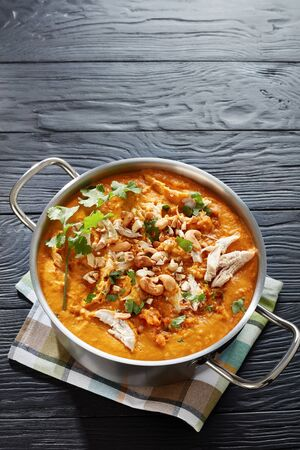 creamy red lentils,  pumpkin and coconut milk soup with pulled chicken breast meat in a metal saucepan on a black wooden table Stok Fotoğraf