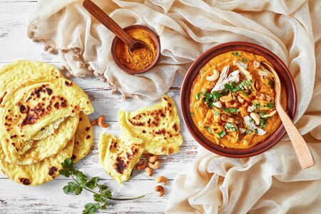 close-up of creamy red lentils pumpkin and coconut milk soup with pulled chicken breast meat in a bowl with chapati  on a white wooden table