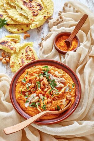 hearty spicy Mulligatawny soup with chicken meat and coconut milk sprinkled with fried cashew in a bowl with chapati on a white wooden table, Indian and english cuisine