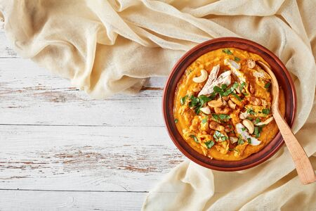 Mulligatawny soup with chicken meat and coconut milk sprinkled with fried cashew in a bowl on a white wooden table with cloth, Indian and english cuisine Imagens