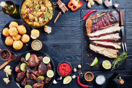 set of caribbean dishes, jerk pork belly, chicken curry, fried dumplings, roasted chicken thighs and drumsticks on plates on a black wooden table, view from above, flatlay