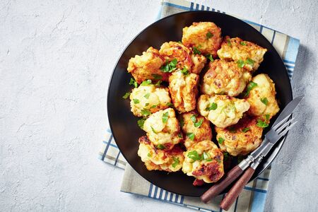 Moroccan tempura-style Fried Cauliflower florets served on a black plate on a concrete table, view from above, close-up, flatlay, empty space
