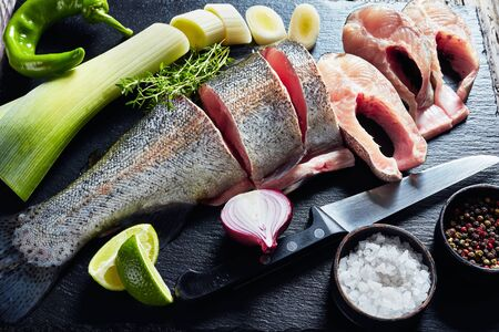 Sliced raw trout with lime wedges, leek, thyme, salt and spices on a black stone cutting board  on an old rustic wooden table Zdjęcie Seryjne