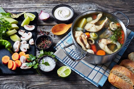 Hot spicy Trout fish soup with vegetables and mushrooms in a saucepan on a wooden rustic table with ingredients