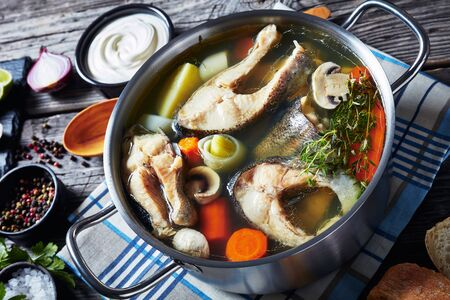 Close-up of hot spicy Trout fish soup with vegetables and mushrooms in a saucepan on a wooden rustic table with ingredients Zdjęcie Seryjne