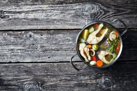 Delicious spicy Trout fish soup with vegetables and mushrooms in a pot on a wooden rustic table, horizontal view from above