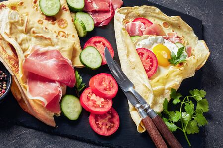 Crepes with fried egg on an old wooden table
