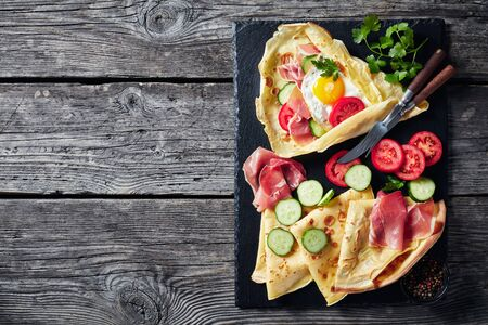 Crepes with fried egg on an old wooden table Foto de archivo - 129247687