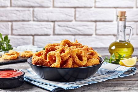 crispy calamari rings, deep-fried breaded squid rings served with tomato sauce in a black bowl