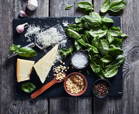 fresh basil leaves, grated parmesan cheese, pine nuts, garlic, peppercorn in a bowl on a rustic wooden table, horizontal view from above, flat lay 写真素材