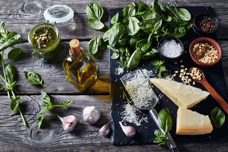 classic Basil pesto sauce in a glass jar. fresh basil leaves, grated parmesan cheese, pine nuts, garlic, peppercorns in a bowl on a rustic wooden table, horizontal view from above, close-up 写真素材