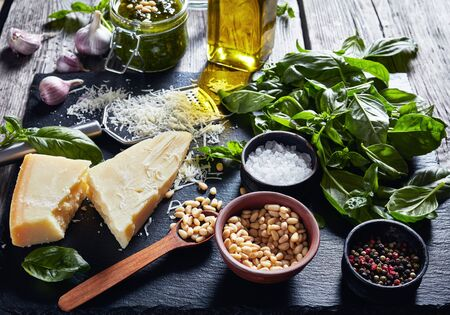 fresh basil leaves, grated parmesan cheese, pine nuts, garlic, peppercorns, bottle of olive oil on a rustic wooden table with homemade Basil pesto sauce at the background, horizontal view from above 写真素材 - 129471079