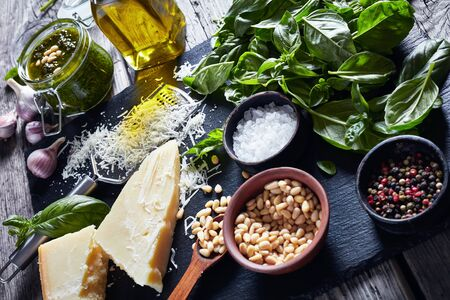 fresh basil leaves, grated parmesan cheese, pine nuts, garlic, peppercorns, bottle of olive oil on a rustic wooden table with homemade Basil pesto sauce, horizontal view from above 写真素材 - 129471093
