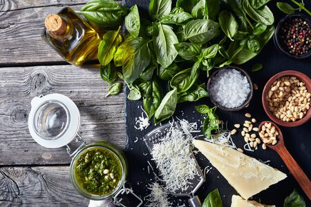 fresh basil leaves, grated parmesan cheese, pine nuts, garlic, peppercorns, bottle of olive oil on a rustic wooden table with homemade Basil pesto sauce in a glass jar. 写真素材