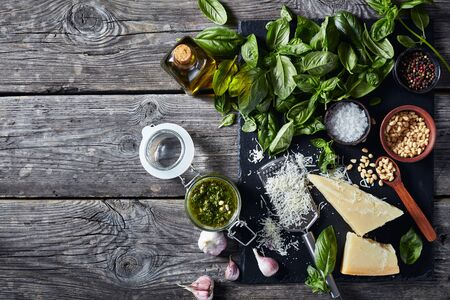 homemade Basil pesto sauce in a glas jar with fresh basil leaves, parmesan cheese, pine nuts, garlic, peppercorns, bottle of olive oil on a rustic wooden table. 写真素材