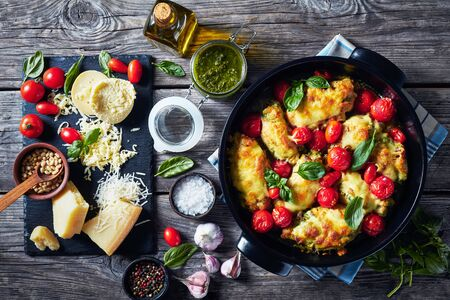 baked Chicken breast rolls filled with basil pesto, tomatoes and cheese in a black ceramic baking dish on a rustic wooden table with ingredients