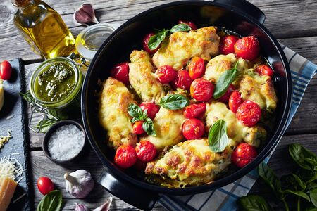 close-up of Italian Stuffed Chicken, chicken breasts rolled up with pesto, tomatoes, and cheese baked in a black ceramic baking dish, horizontal view from above