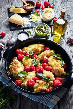 close-up of Italian Stuffed Chicken, chicken breasts rolled up with pesto, tomatoes, and cheese baked in a black ceramic baking dish, vertical view from above