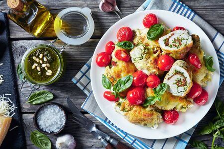 hot Italian Chicken Roll-Ups with pesto, cheese and tomatoes on a white plate with ingredients on a wooden table, horizontal view from above Imagens
