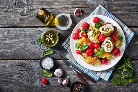 Italian Chicken Roll-Ups with pesto, melted cheese and tomatoes on a white plate with ingredients on a wooden table, horizontal view from above, flat lay, copy space