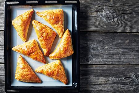 freshly baked puff pastry apple turnover on a silicon mat on a baking tray, horizontal view from above, flatlay, close-up, copy space