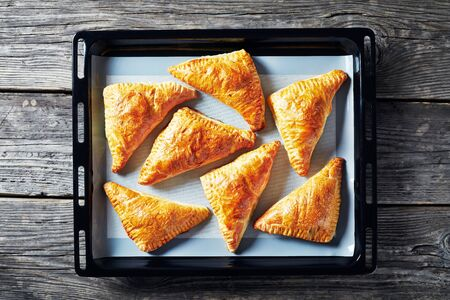homemade freshly baked puff pastry apple turnover on a silicon mat on a baking tray, horizontal view from above, flatlay, close-up