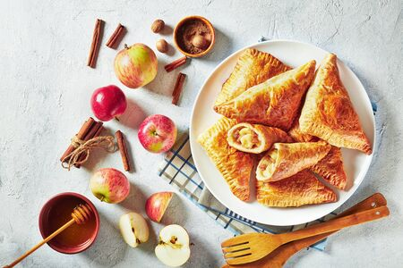 apple turnover on a white plate on a concrete table with ingredients, horizontal view from above, flatlay Archivio Fotografico