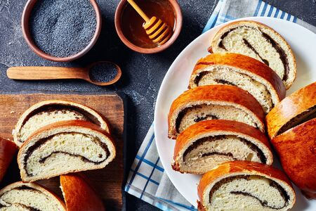 Poppy cake, Makovnjaca, sweet dough roulade with poppy seeds filling, sliced on a white plate on a concrete table, croatian cuisine, horizontal view from above.