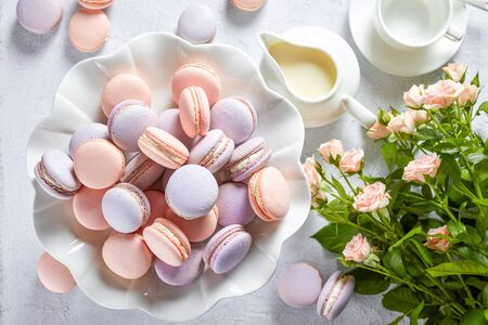 close-up of french macaroons on a porcelain cake stand and some on a white concrete table with bouquet of fresh flowers, coffee cup and creamer, horizontal view, flat lay