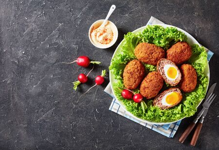 scotch eggs, boiled eggs wrapped in minced sausage served with lettuce and radish on a plate on a grey concrete table with a bowl of mayonnaise paprika sauce, view from above, flat lay, free space