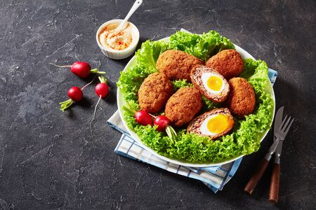 scotch eggs, boiled eggs wrapped in minced sausage, served with lettuce and radish on a plate on a grey concrete table with mayonnaise sauce.