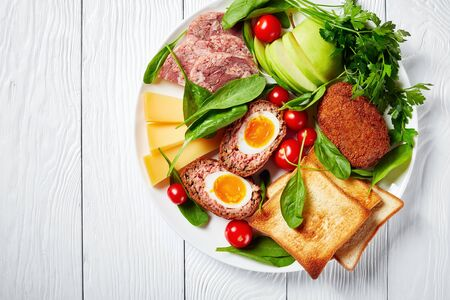 Ploughman's lunch of toasts, cheddar cheese, apple, scotch eggs, sliced headcheese, tomatoes, spinach, hot mustard  and pickled onion on a white plate 写真素材