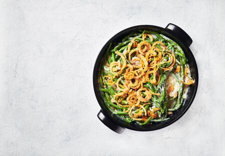delicious Green Bean Casserole sprinkled with crispy fried onions in a black dish on a concrete table, american cuisine, view from above, flatlay, free space Stock Photo
