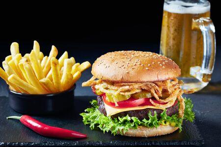 Close-up de hamburguesa con queso con empanada de ternera, queso cheddar, cebollas fritas crujientes, lechuga, tomates en rodajas, encurtidos sobre tablero de piedra con papas fritas y cerveza en una taza de vidrio en el fondo negro