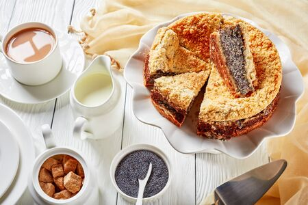 delicious sliced Poppy Seed Crumble Cheesecake on a white platter served with a cup of English tea with milk on a wooden table, horizontal view from above, close-up Zdjęcie Seryjne