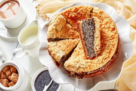 close-up of delicious sliced Poppy Seed Crumble Cheesecake on a white platter served with a cup of English tea with milk on a wooden table, horizontal view from above Stock Photo