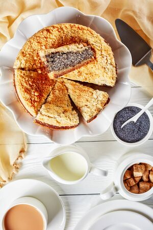 delicious Poppy Seed Crumble Cheesecake slice on a white platter with a cup of English tea with milk on a wooden table, horizontal view from above Stock Photo