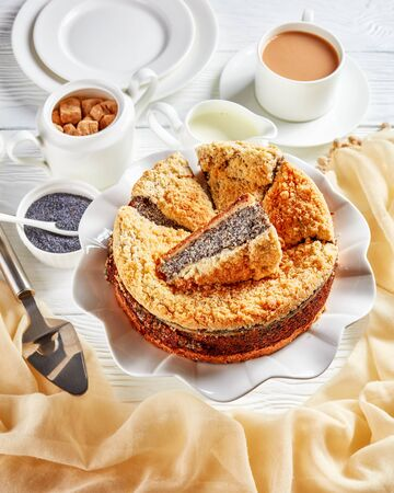 close-up of delicious sliced Poppy Seed Crumble Cheesecake on a white platter served with a cup of English tea with milk on a wooden table, vertical view from above