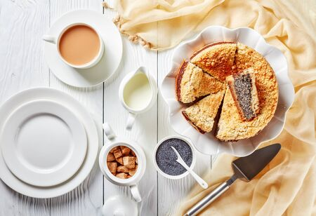 delicious sliced Poppy Seed Crumble Cheesecake on a white platter served with a cup of English tea with milk on a wooden table, horizontal view from above