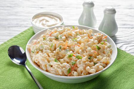 primo piano della tradizionale insalata di maccheroni con carote grattugiate, sedano, cipolline e condimento per maionese in una ciotola bianca su un tavolo di legno bianco