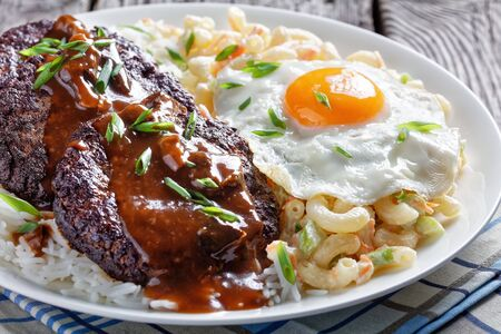 loco moco of white rice, topped with a hamburger patty, a fried egg, brown gravy, and macaroni salad served on a white plate on a rustic wooden table, Hawaiian cuisine, view from above,