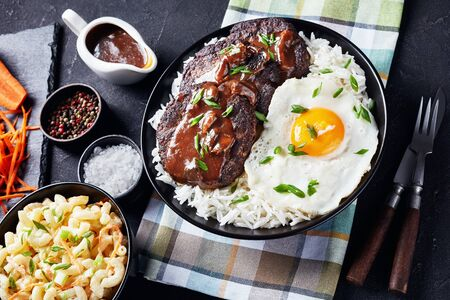 loco moco of white rice, topped with a hamburger patty, a fried egg, brown gravy, and macaroni salad served on a black plate on a concrete table, Hawaiian cuisine, view from above, close-up Stock Photo