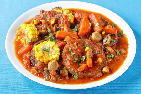 close-up of Simmered burgers with Tomato Sauce, with mushrooms, veggies and corn kernels on a white plate on a blue textile mat Foto de archivo