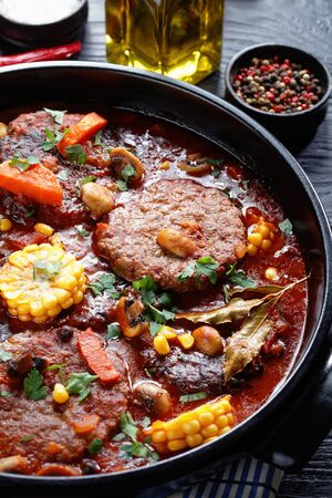 close-up of Meatloaf Burgers stewed in marinara sauce, with mushrooms, veggies and corns in a black ceramic dutch oven with ingredients on a black stone board on a wooden table, vertical view