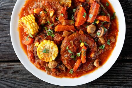 homemade burgers stew in tomato sauce, with mushrooms, veggies and corn kernels on a white plate on a wooden table, horizontal view, flatlay, close-up