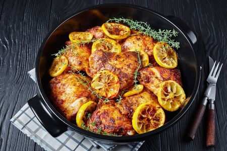 baked Chicken Thighs With Roasted Lemon Slices and thyme in a black ceramic dutch oven on a wooden table, horizontal view from above