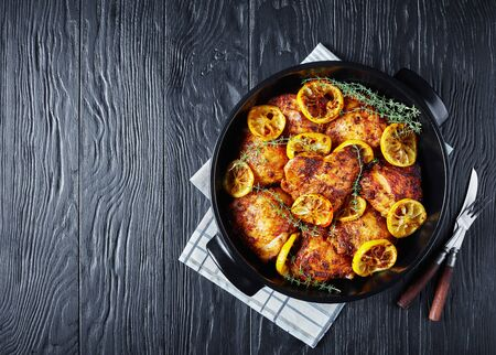 delicious Chicken Thighs With Roasted Lemon Slices and thyme in a black ceramic dish on a wooden table, horizontal view from above, flatlay, free space