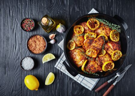 delicious Chicken Thighs With Roasted Lemon Slices and thyme in a black ceramic dish on a wooden table, horizontal view from above, flatlay, copy space